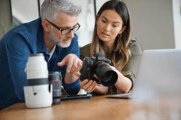 Photographers in office checking on picture shots