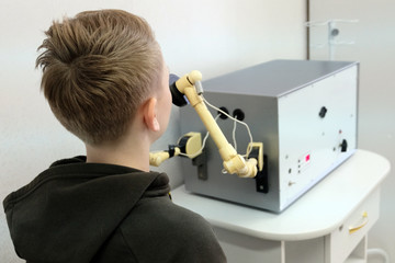 A teenager in a jacket with a hood on a physiotherapy procedure UHF in a hospital. An ultra high frequency medical device warms up the boy's nose.