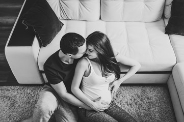 Image of husband sitting and holding belly of pregnant wife hands. Woman, girl and man kissing and hugging tummy at home. Loving Couple. Parenthood concept. Baby Shower. Black and white Family photo.
