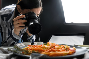 Young woman taking picture of tasty pasta in professional photo studio