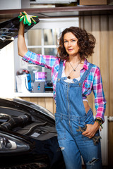 smiling woman as a mechanic in a garage