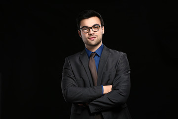 Portrait of handsome young businessman on dark background