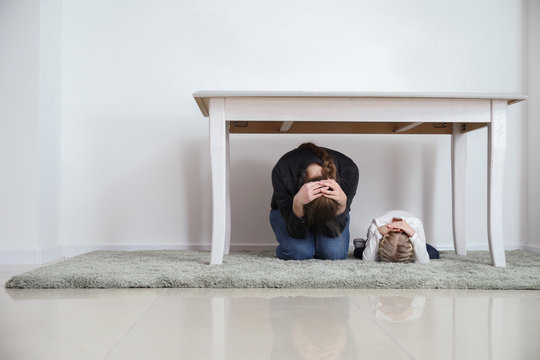 Mother with daughter under table during earthquake indoors