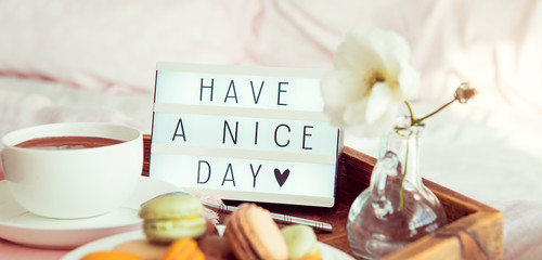 Close up Have a nice day text on lighted box on the tray with breakfast in bed. Cup of coffee, macaroons, flower in vase. Good morning mood. Hospitality, care, service concept. Wide banner. Copy space