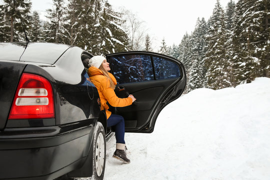 Young woman getting out of car at snowy winter resort