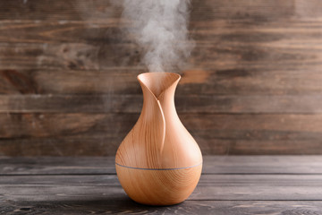 Aroma oil diffuser on wooden background Fototapete