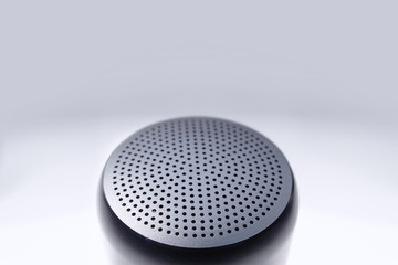 Top view of wireless speaker showing black metal grille - soft floating effect - plain white background - copy space
