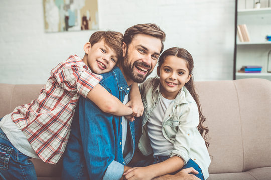 Handsome father is playing and have a fun with his little son and daughter at home on the couch. Happy family. Best father