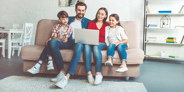 Happy beautiful family with laptop on the couch at home in casual clothes