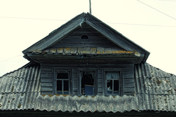 Photo of the roof of a village house with three destroyed windows and tiled in dramatic style