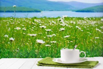 Coffee cup against blooming meadow