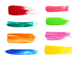 Set with abstract brushstrokes of different bright paints on white background, top view