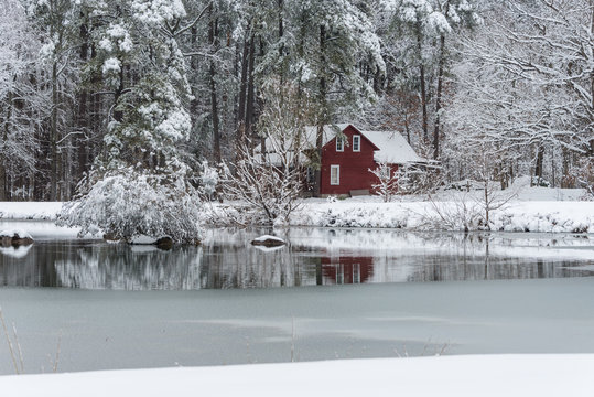 Red house in snow behind a frozen pond
