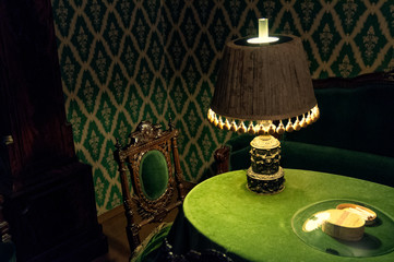 Green table with the lamp on in a green room