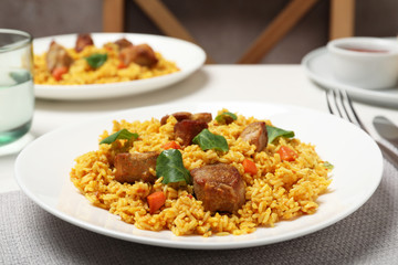 Plate of delicious rice pilaf with meat on table