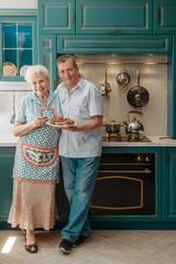 Joyful grandparents in their kitchen