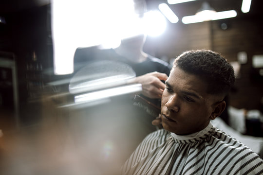 The fashion barber in black clothes  makes a razor cut hair for a stylish black-haired man sitting in the armchair in a stylish barbershop