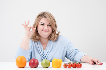 Young curvy fat woman in casual blue clothes on a white background at the table and shows OK, vegetables and fruits are laid out in front of her in a row. Diet and proper nutrition.
