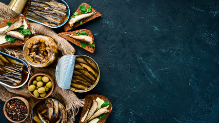 Assortment of sprats in oil. Smoked fish On a black background. top view. Free copy space.