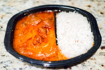Orange red curry tikka masala sauce macro closeup, with white basmati rice in black plastic tv dinner fast food frozen quick meal container on table