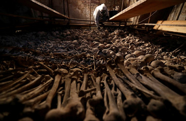 An archaeologist collects human bones as part of a restoration work in an effort to preserve the Sedlec Ossuary in Kutna Hora