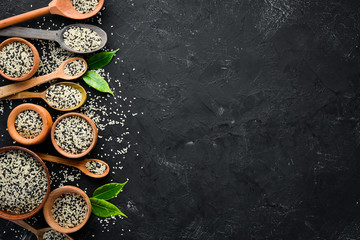 Sesame. Set of black and white sesame seeds. On a black background. Top view. Free copy space.