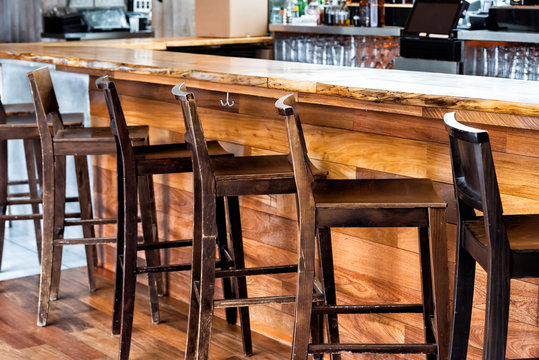 Row of empty wooden vintage bar stools by counter in drink establishment pub during day pattern closeup rustic retro wood and nobody