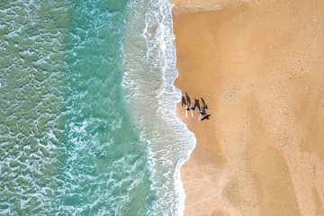 Small group of wave surfers and surf boards standing on a sandy beach in front of The Mediterranean Sea - Top down aerial image.