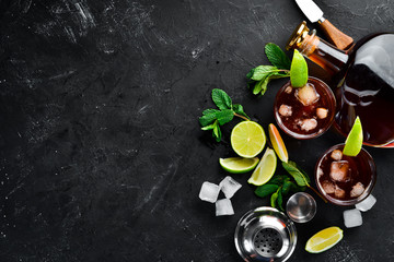 Alcoholic Beverage Rum, lime and mint on a black stone background. Top view. Free space for your text.
