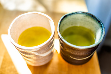 Wooden table in house room with morning sunlight and two cups filled with Japanese vibrant green yellow oolong tea color in breakfast container