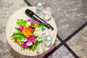 Colorful bouquet on wooden table with glasses and wireless microphone