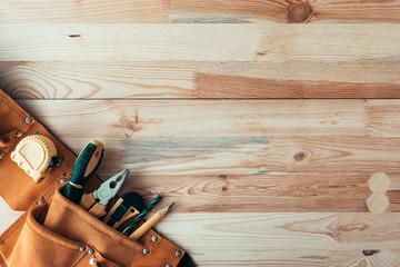 Fototapeta Carpentry tool belt on woodwork workshop desk, top view obraz