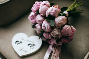 Beautiful  Wedding bouquet of pink tulips and Handmade wooden heart for the wedding rings