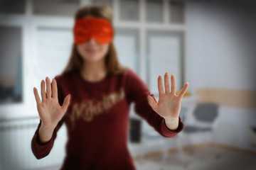 The girl comes with a blindfolded eyes blindly to the touch.