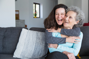 Portrait of happy mid adult woman embracing her senior mother