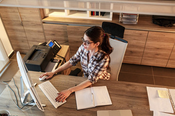 Casual outfit businesswoman in her office.She sitting at the desk and using computer.