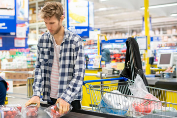young man pays for purchases at the checkout in the store