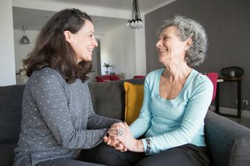 Joyful senior woman and her daughter chatting