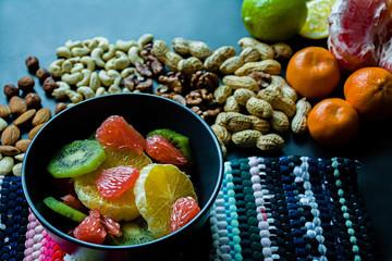 Fruit, citrus salad of grapefruit, kiwi, orange, banana. Adorned with fresh citrus fruits and assorted nuts. Proper nutrition. Healthy food. Side view. Dark background.