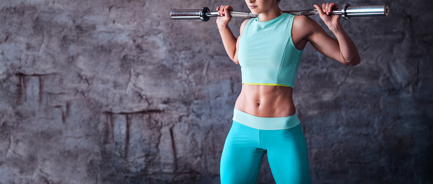 Cropped image of an athletic woman in sportswear workout with a barbell in the gym against a gray wall