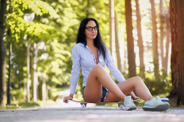 Portrait of a beautiful girl in a white shirt and shorts sitting on a skateboard in the park on a summer sunny day