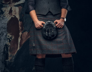 Traditional Scottish costume. Kilt and sporran. Studio photo against a dark textured wall
