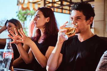 Young people relax in the restaurant or cafe outdoor, drink beer and talking