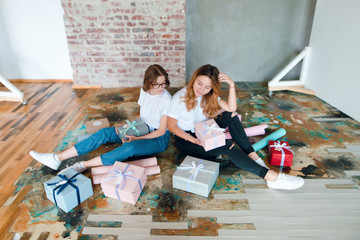 Two beautiful girls sitting on the floor and packing presents. Gift boxes. Birthday, holiday concept.