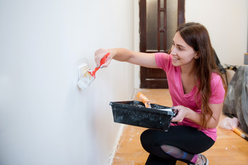 Young smiling woman painting walls with a roller in a new house. Interior design. Renovation