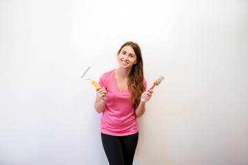 Young attractive woman standing near the wall with a roller and paintbrush in a new house. Interior design. Renovation