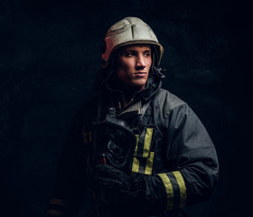 Brutal firefighter in uniform and safety helmet holding an oxygen mask and looking sideways with a confident look. Studio portrait in a dark studio against a textured wall.