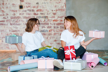Two smiling girls sitting together, packing gifts and having fun. Present concept. Friends