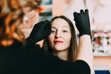 Cosmetologist client plucks eyebrows thread before the procedure microbleeding