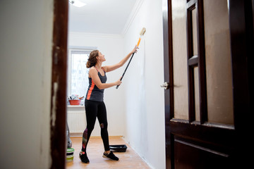 Young brunette woman painting walls with a roller in the room. Interior design. Renovation